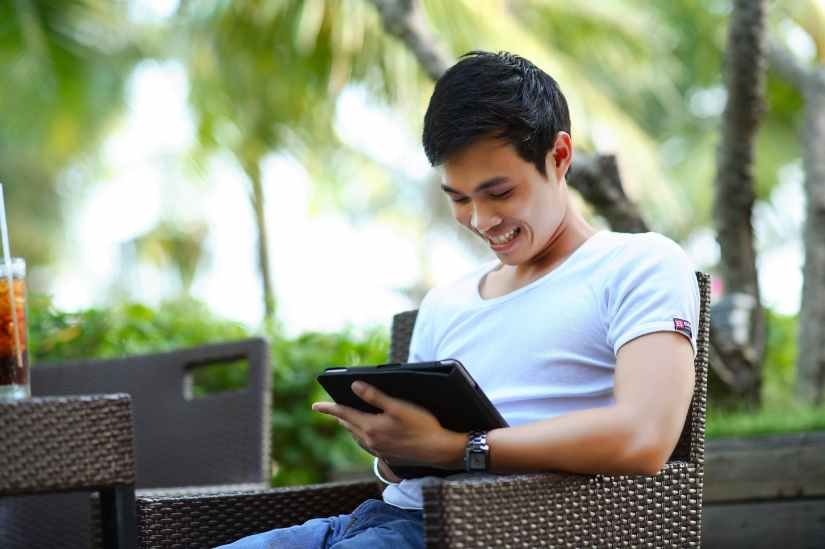 man in white shirt using tablet computer shallow focus photography